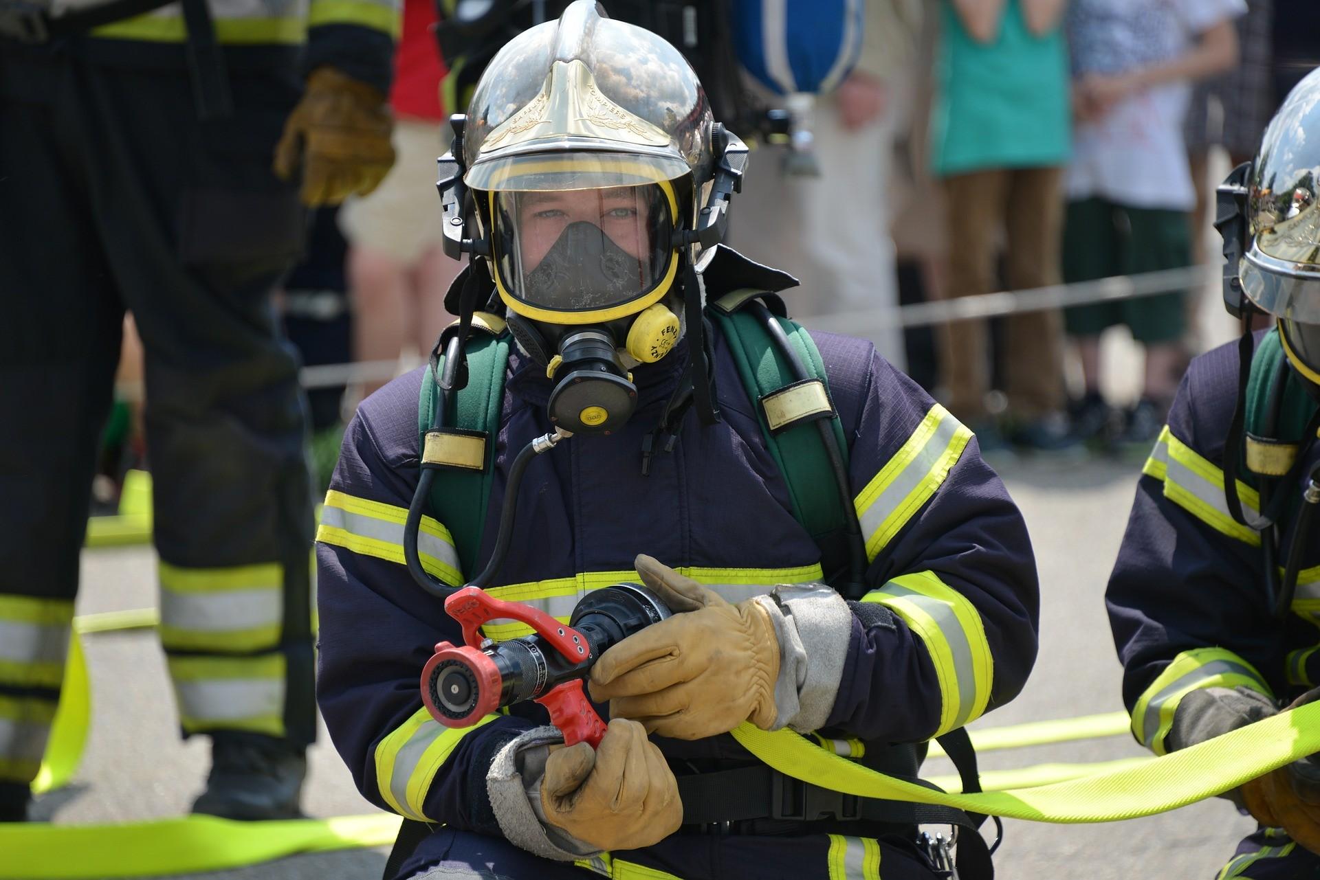 sapeurs pompiers avec lance à incendie